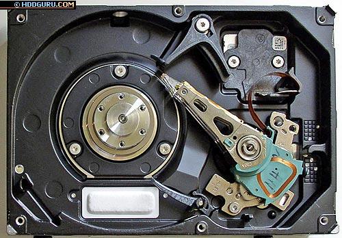 Внутреннее устройство системы позиционирования накопителя Seagate Barracuda 7200.7, 160 GB. Виден пакет магнитных головок, ось, на которой установлен БМГ, катушка VCM, парковочные механизмы, ограничители